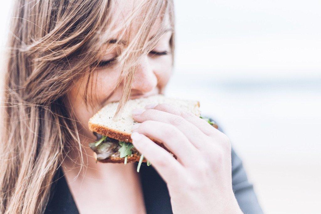 Una ragazza bionda in primo piano mentre mangia un toast